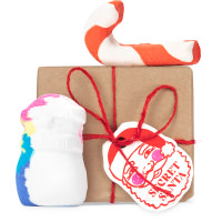 a lush gift set with red ribbon on pink background