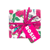 A square gift with pink toned floral wrapping paper, a pink ribbon and a pink tag that reads 'Rosie Gift'.