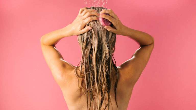 A person with blonde hair using LUSH Snow Fairy Shampoo Bar in their hair in the shower. The shampoo bar is round and pink .