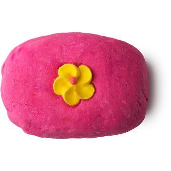 Unser zuckersüßes Creamy Candy Schaumbad ist pink und wird von einer Zuckerblume geschmückt