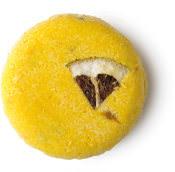 Montalbano ist ein gelbes, festes Shampoo ohne Verpackung mit einem dekorativen Stückchen Zitrone auf der Oberfläche