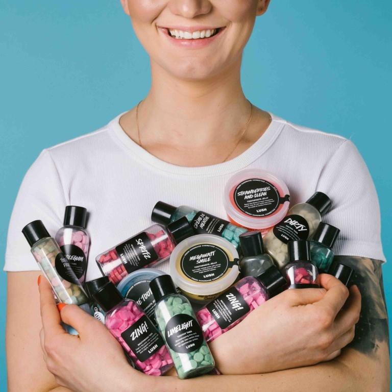 Kvinna som håller massa burkar med tandprodukter i famnen