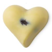 Herzförmiger, weißer Massage Bar mit dunkler Kakaofüllung, die an der Oberfläche durchscheint