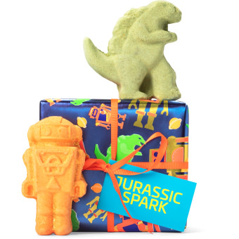 Un regalo de Navidad con envoltorio regalo azul de dinosaurio y robot con 2 productos para el baño en forma de dinosaurio y robtot alrededor