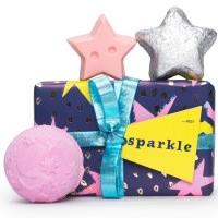 ein dunkelblaues Geschenk mit rosa-farbenen Sternen, einer hellblauen Schleife und 2 Sternförmigen Produkten und einer Badekugel