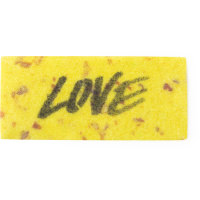 A bright yellow speckled washcard featuring the word love