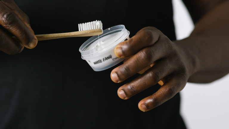 white fang being used with bamboo toothbrush