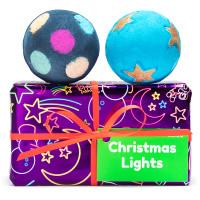 Una caja de regalo de color rosado con una bomba de baño de color negro y otra de color azul con estrellas de navidad encima de la caja