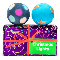 A purple gift with a black and multicoloured bath bomb being taken out