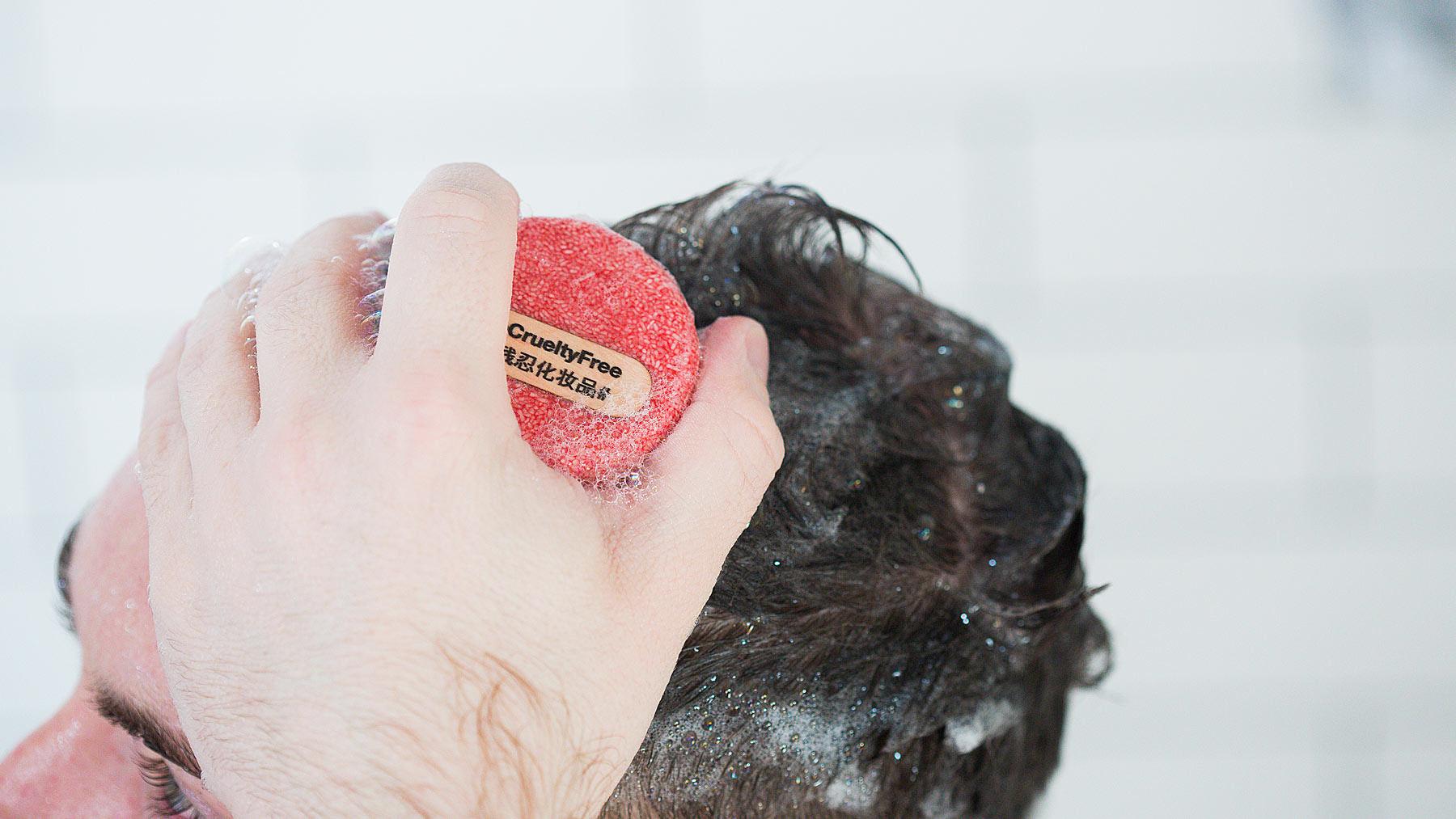 Una persona utilizza lo shampoo solido New sui suoi capelli