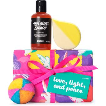 Regalo de navidad de con estampado de aves color rosa, amarillo y morado rodeado de productos cosméticos