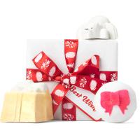 Un regalo de navidad con envoltorio regalo clásico de color blanco con un lazo rojo y productos para el baño alrededor