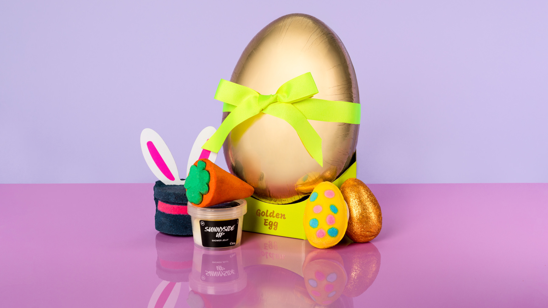 golden egg shaped box surrounded by products that come inside the gift. The background is a light purple