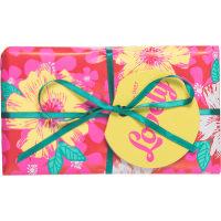 Ein rosafarbenes Geschenk mit gelben Blumen und einer grünen Schleife dekoriert