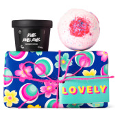 dark blue gift box with flower and ball pattern on it and products around it