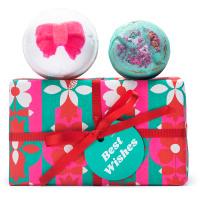 Una caja de regalo de navidad de color verde y rojo con bombas de baño encima