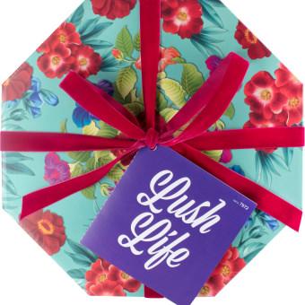 Türkise Hutbox mit Blumenprint und einer roten Schleife
