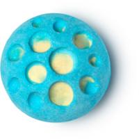 Eine blaue Badebombe mit Löchern die das gelbe Innere sichtbar machen