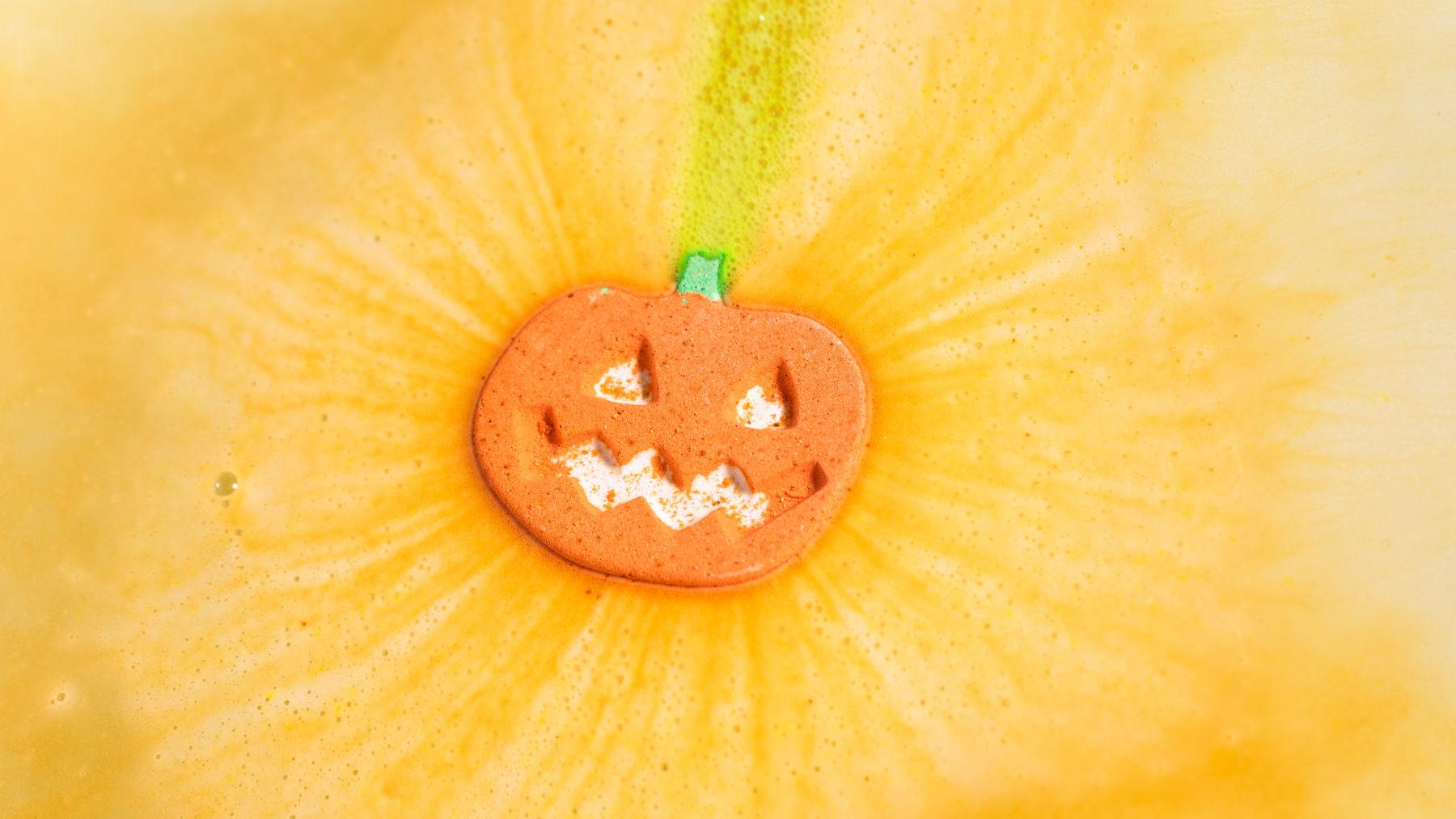 A orange fizzing pumpkin shaped bath bomb in water