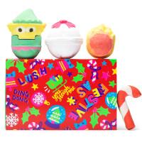 Una caja de navidad de color rojo, verde y amarillo con bombas de baño en forma de elfo, fuego y campana encima