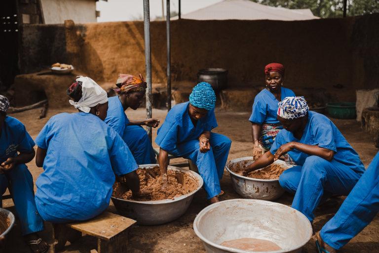 Fem kvinnor vispar den bruna nötsmeten med händerna