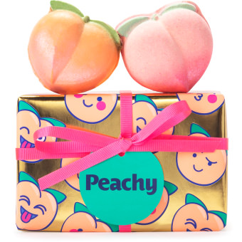 golden wrapped present with peach illustrations and products on top