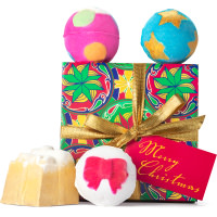 Un regalo de navidad reutilizable de color navideño verde, rojo y amarillo con un lazo dorado y bombas de baño alrededor