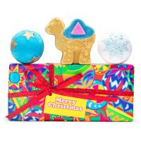 Una caja de regalo multicolor con un lazo de color rojo y 3 bombas de baño encima