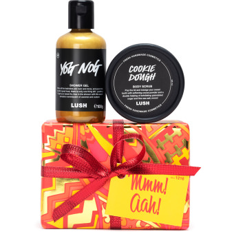 Yellow orange and red patterned present with shower gel and body scrub on top on white background
