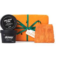 Un regalo de navidad con envoltorio regalo naranja y un lazo verde con productos cosméticos alrededor