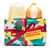 Una caja de regalo de navidad con un diseño verde arbol de navidad y un lazo rojo con una bomba de baño en forma de ajo y otra en forma de regalo sorpresa encima