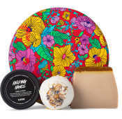 red gift tin with floral theme and products around it