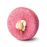 A  light pink, round shampoo bar with a rose petal in the centre