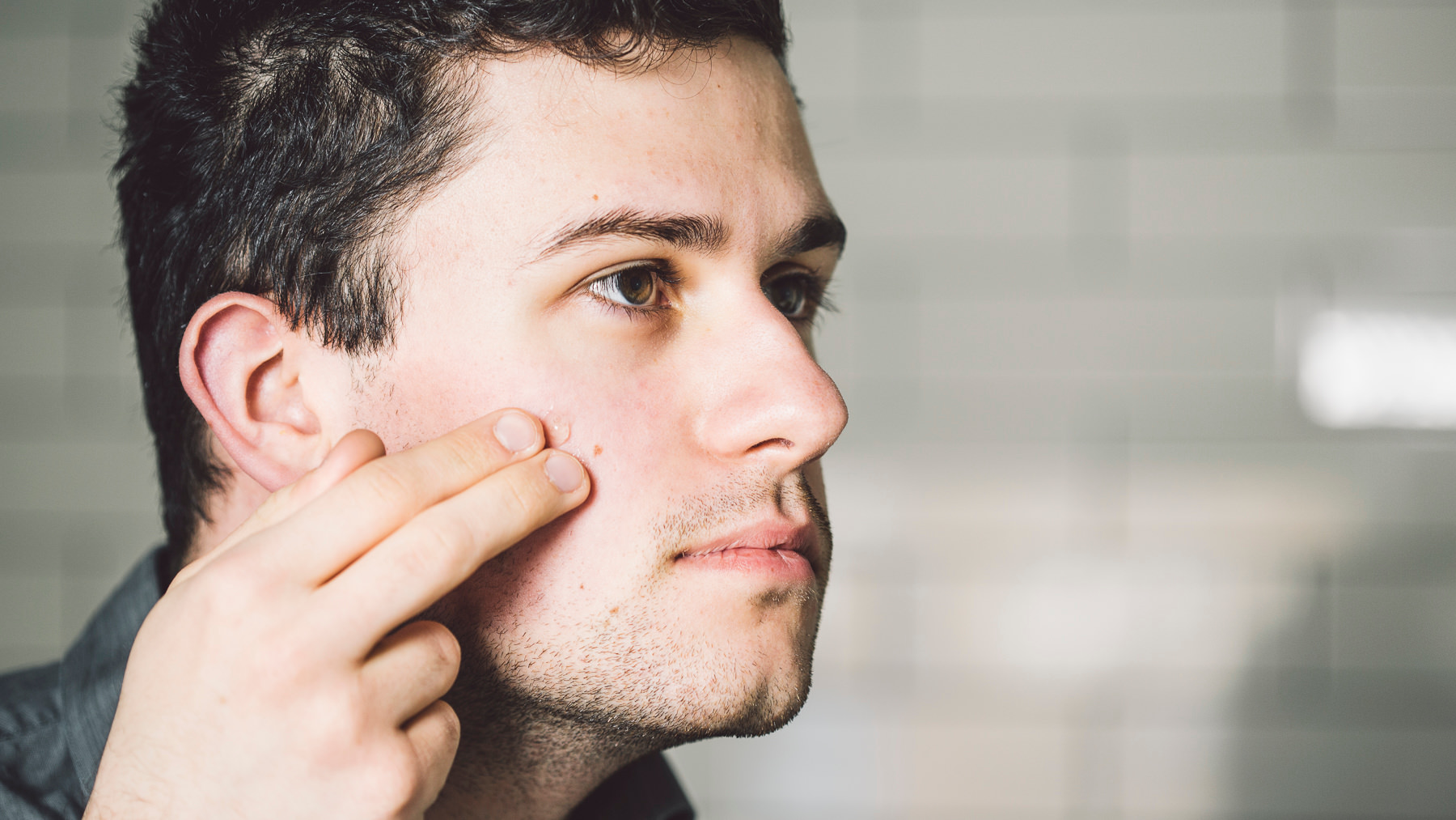 A man applying product on his face