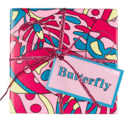 Die Geschenksbox mit Deckel ist rosa, mit Schmetterlingsflügeln in Pink, Gelb und Blau bedruckt und mit einer pinken Schleife zusammengebunden