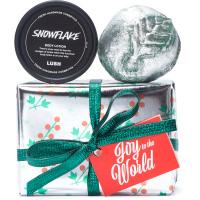 Una caja de navidad de color plateado con un diseño de color verde y rojo navideño y lazos verders con encima un jabón en forma de manzana y una hidratante corporal