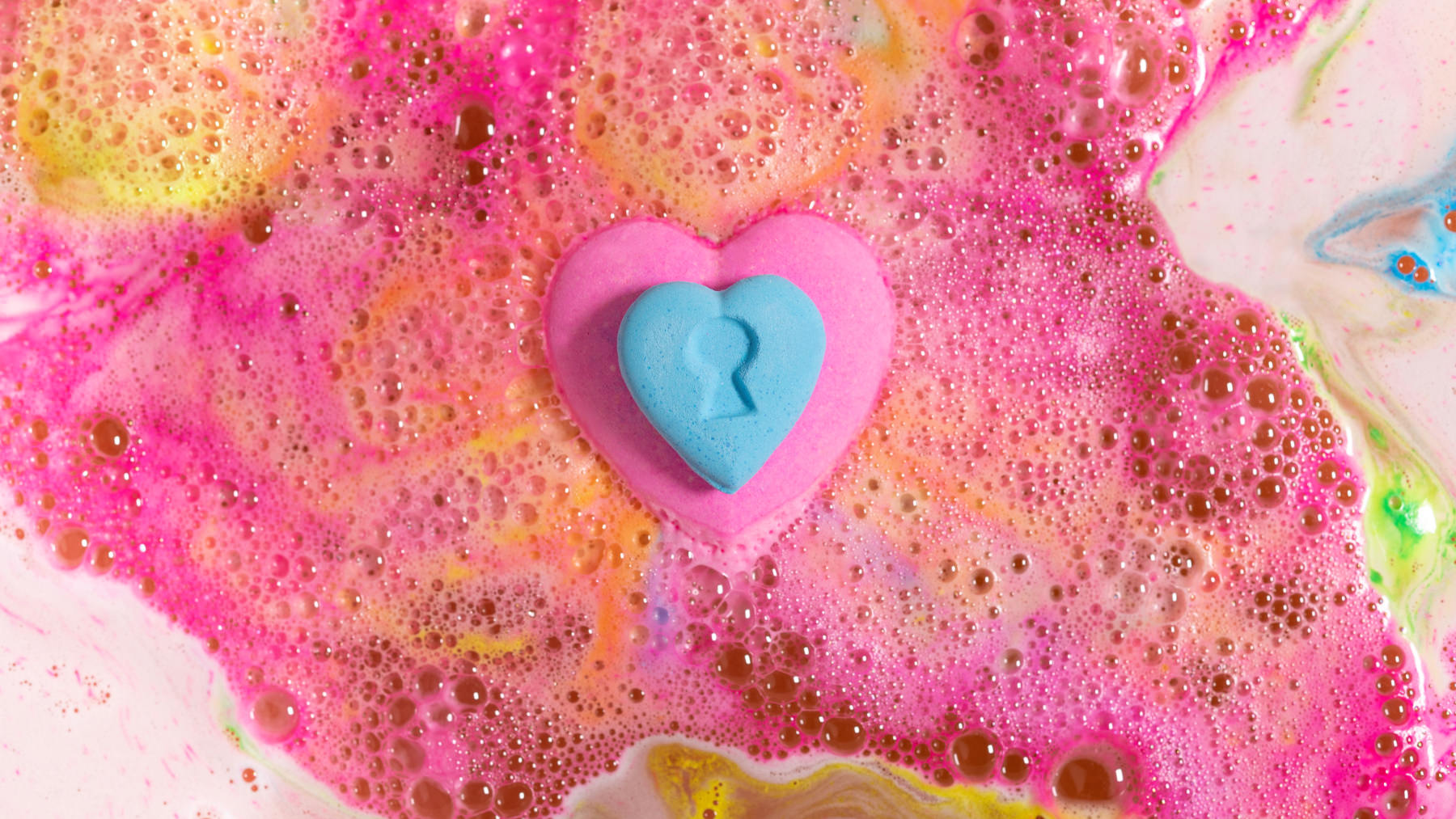 heart shaped amazeball bath bomb surrounded by its own bright pink and orange foam