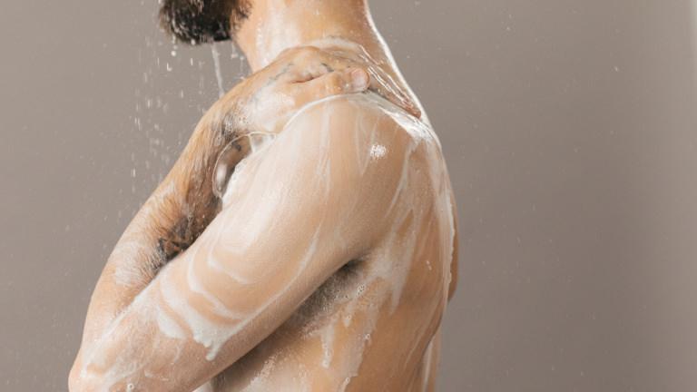 A person using a white shower cream