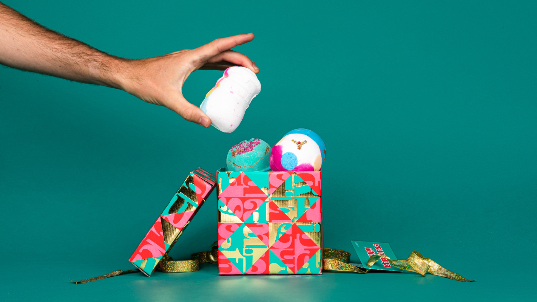 pink and green gift with hand taking out bath bombs on green background
