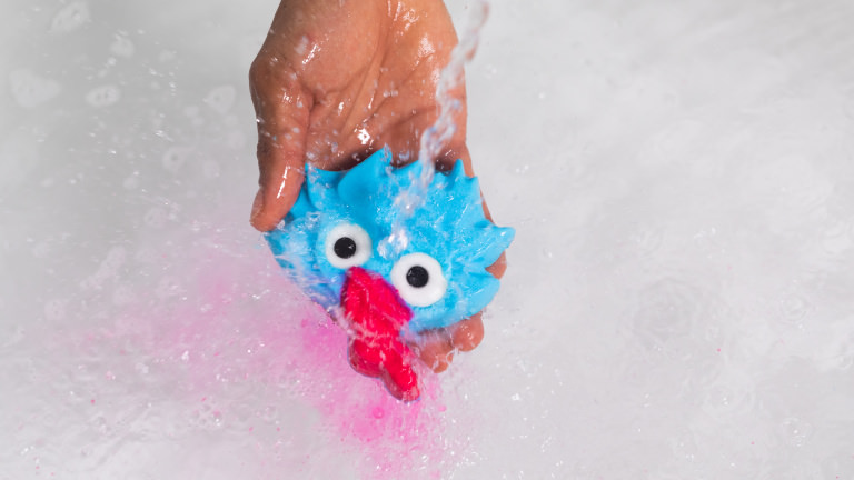 blue goblin with long tongue bubble bar being held under running water