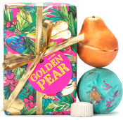 Green, pink, gold and blue patterned present with gold Ribbons with a bath bomb, a bath oil and a soap to the right hand side of present on a white background