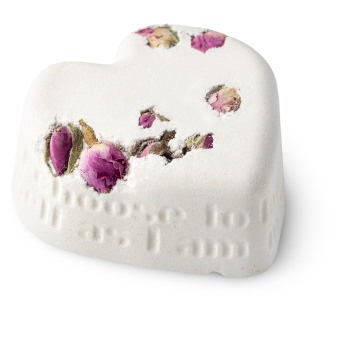 white heart shaped bath bomb with dried roses embedded into it