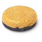 circular shampoo bar with black coloured bottom and yellow coloured top