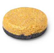 circular shampoo bar with black coloured bottom and yellow coloured top