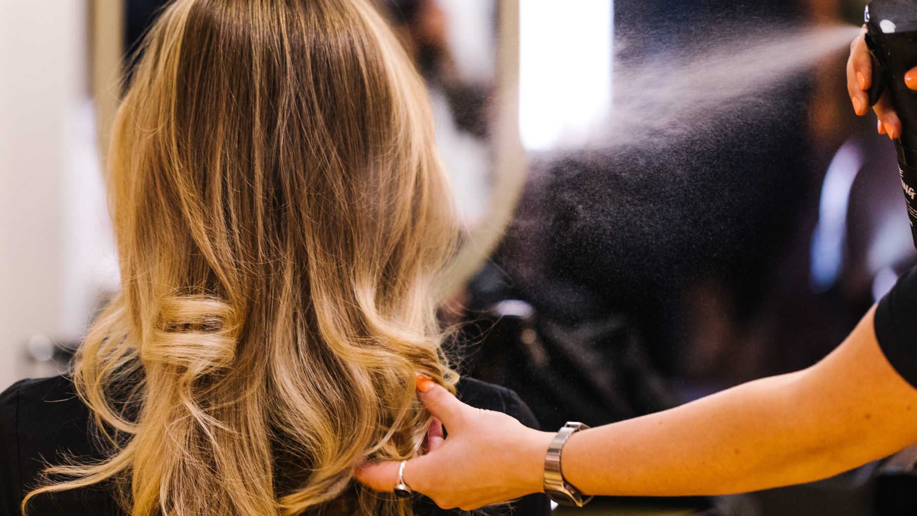 An image of a person with long blond hair on heir back, their hair is being sprayed with product