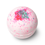 A pale-pink, spherical bath bomb with dark pink spots and blue salt on top