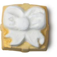 Eine Badebombe in Form eines goldenen Geschenkspaketes mit Schleife
