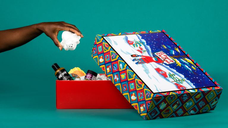 A opened red square gift on green background with bear being taken out by hand