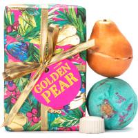 Una caja de regalo de navidad de color verde, rosa, dorado y azul con lazos dorados con dos bombas de baño encima