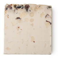A square piece of cream coloured soap with dried apricots, cranberries and currants throughout